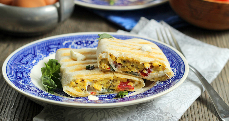 Breakfast burrito cut in two on a plate