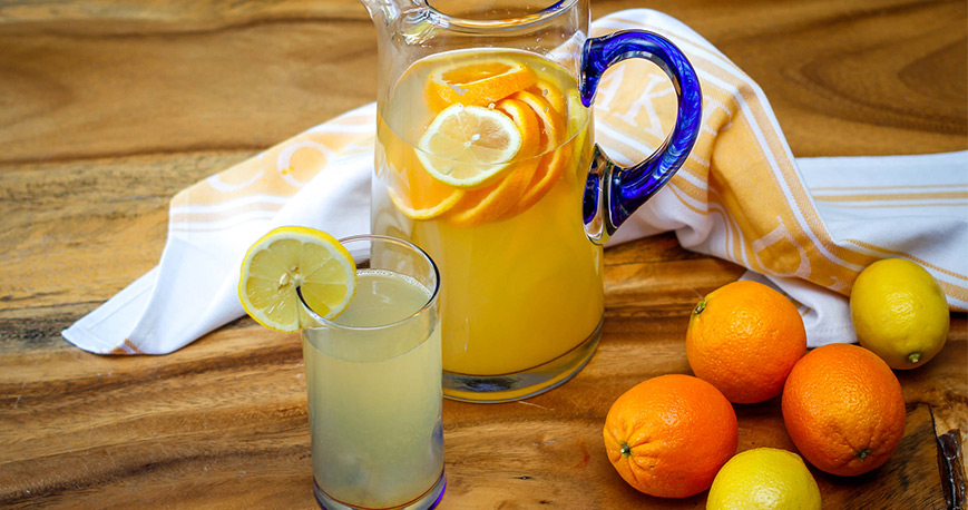 Pitchenr and glass of lemonade with oranges and lemons beside