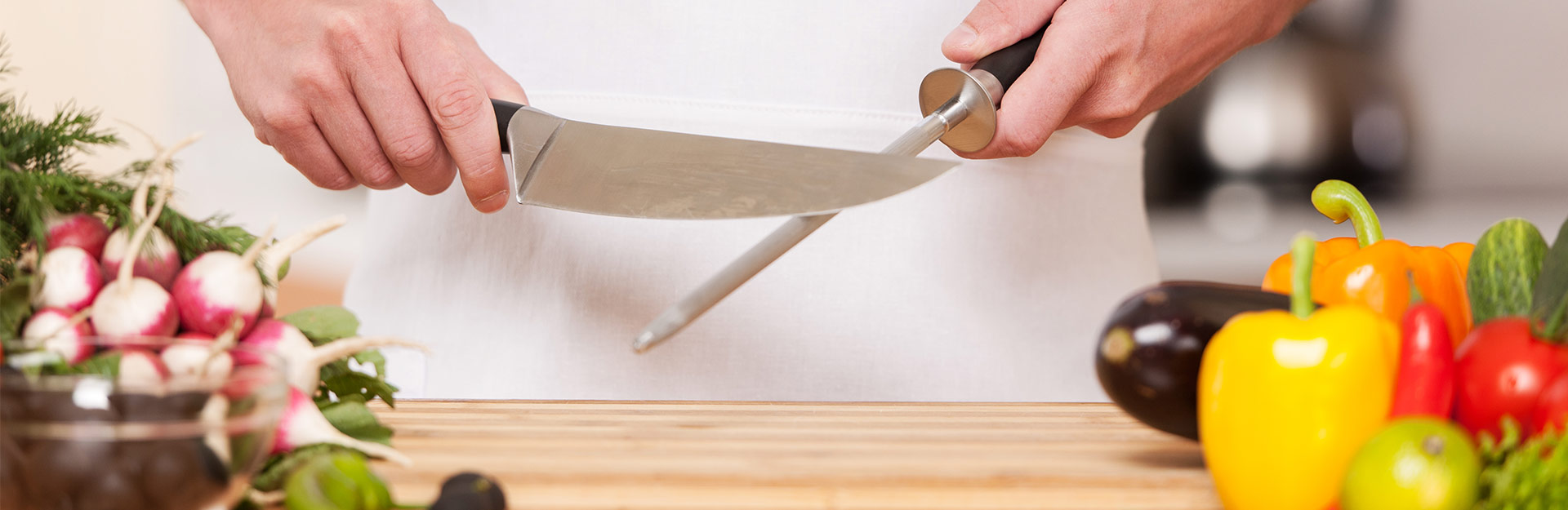 Holding knife and honer over cutting board with vegetables
