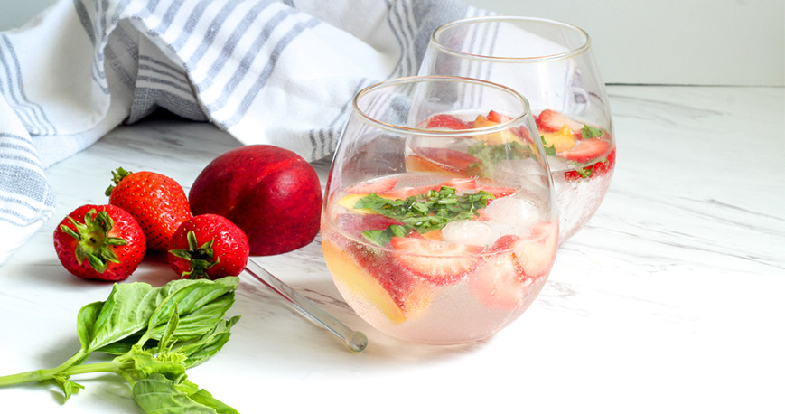 Two glasses of sangria with strawberries beside