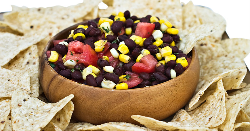 Black beans, corn, tomatoes in bowl with tortilla chips around