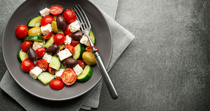Tomato, feta cheese, cucumber and black olives in a bowl