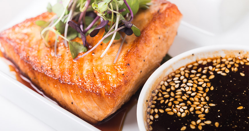 Bowl of teriyaki sauce beside cooked salmon