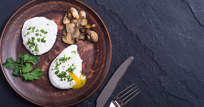 Two poached eggs on a plate with sauteed mushrooms