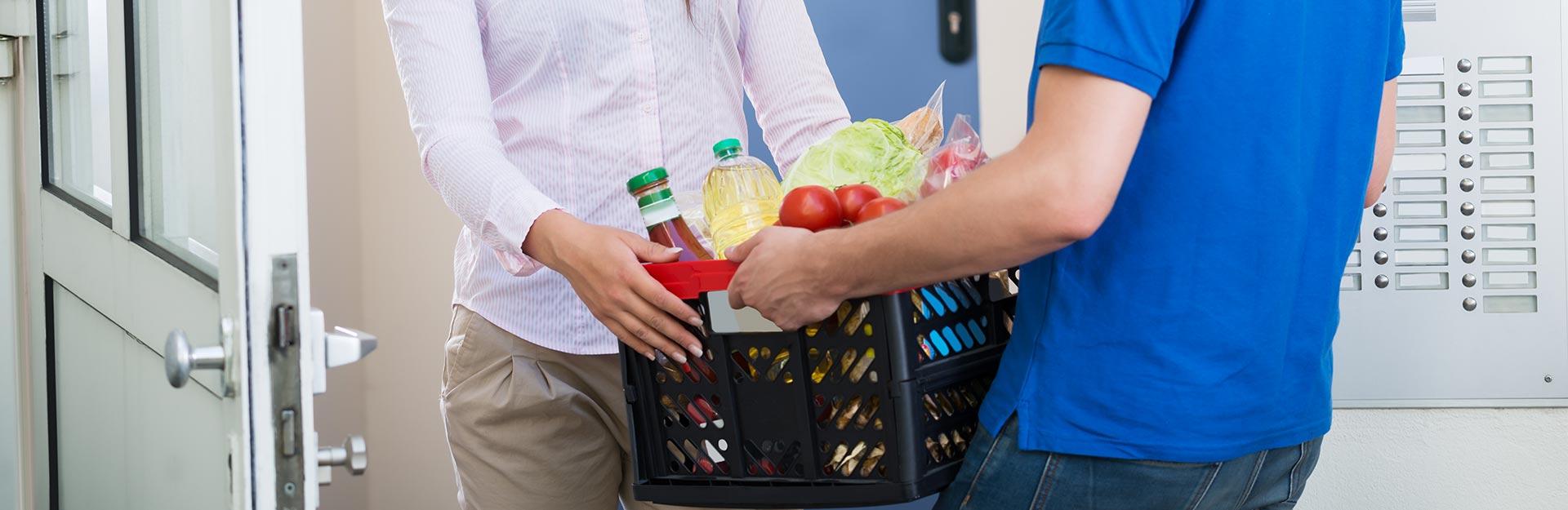 Man handing woman box of groceries