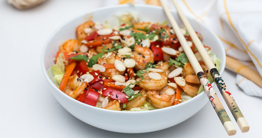 A salad with shrimp in it and chop sticks resting on bowl
