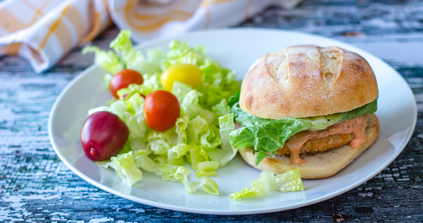 salmon burger on a plate with garden salad