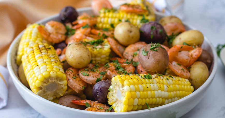 potatoes, corn, shrimp and other ingredients presented in a bowl