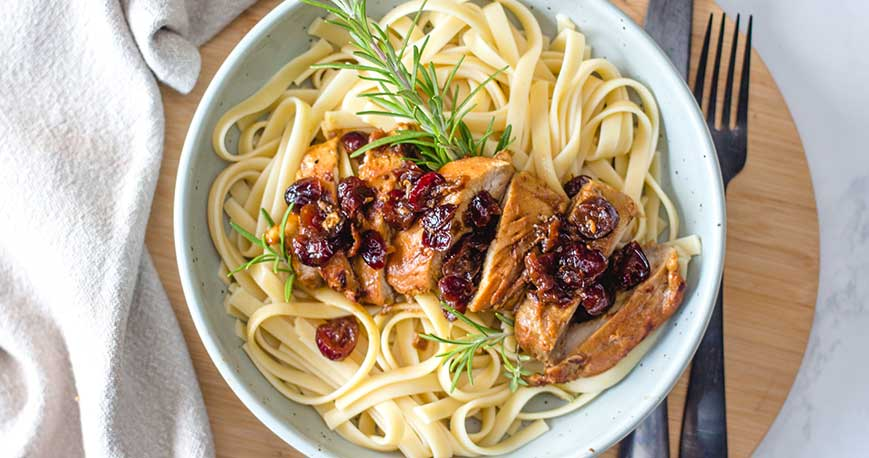 Cranberry roasted balsamic chicken on top of a bowl of pasta