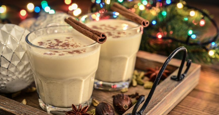 two glasses of two glasses of homemade eggnog recipe on a holiday themed wooden board
