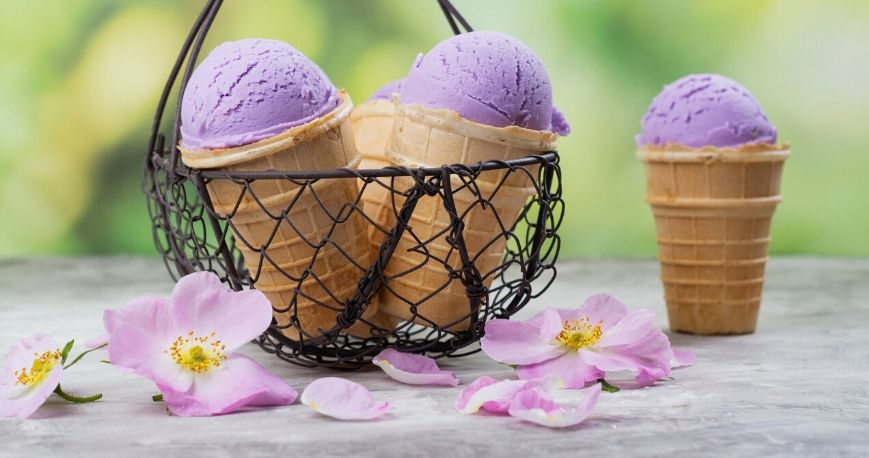 purple ube ice cream in cones with flowers around a basket