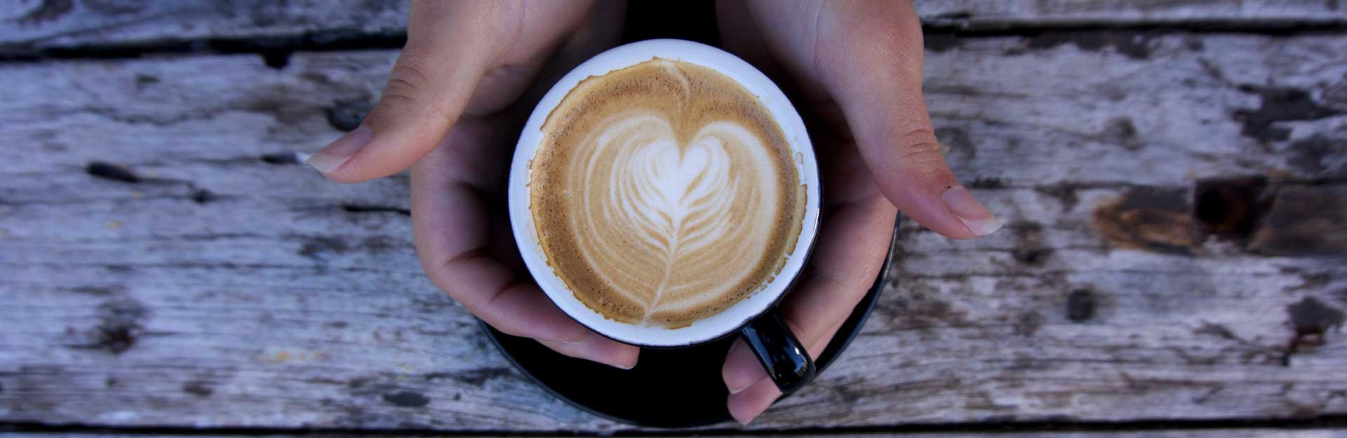 hands holding a cappuccino: an example of a recipe that can be made with oat milk vs almond milk