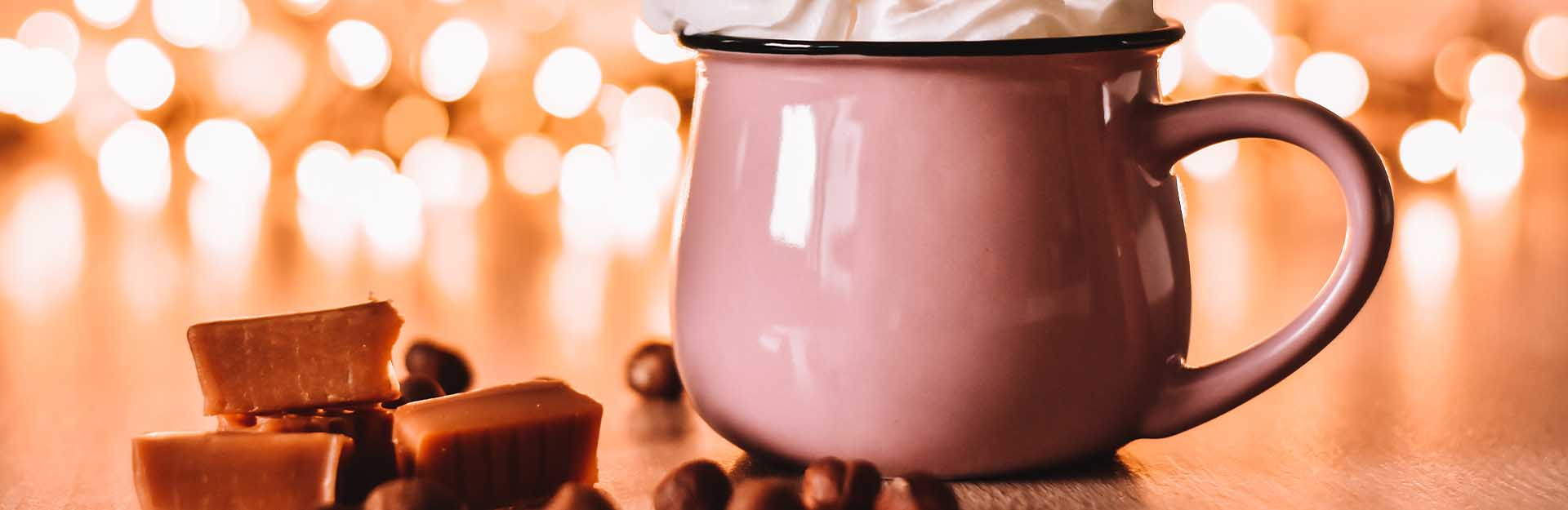 A pink mug of hot chocolate sitting next to cubes of caramel.